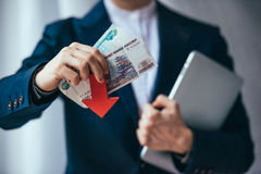 Devaluation. Business person holds roubles and red arrow. Devaluation of the Russian rouble Royalty Free Stock Images