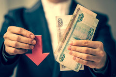 Devaluation. Business person holds roubles and red arrow. Devaluation of the Russian rouble.  Toned picture Stock Photo