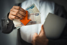 Devaluation. Business person holds roubles and red arrow. Devaluation of the Russian rouble.  Toned picture Stock Photography