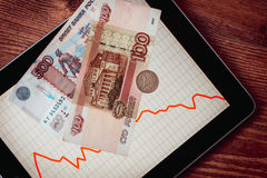 Devaluation. Coins and banknotes of russian roubles on tablet with fluctating graph. Devaluation of the Russian rouble.  Toned picture Stock Image
