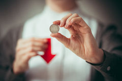 Devaluation. Person holds rouble coin and red arrow. Devaluation of the Russian rouble Royalty Free Stock Image