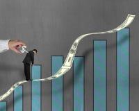 Devanadera de la bobina en la situación trasera del hombre de negocios en el dinero creciente t Foto de archivo