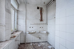 Devastated bathroom full of dirt and dust. Bathroom in the destroyed building royalty free stock photography
