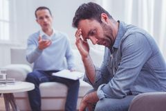 Devastated bearded man touching his forehead during psychological therapy. Cannot cope with problems. Profile of devastated bearded men sitting on sofa and stock image