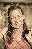 Devastated Woman stressed at prison fence. Portrait of stressed mature woman behind mesh wire fence, with desperate, sad, crying facial expression stock photography