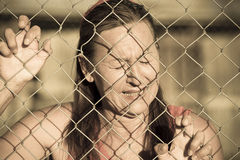 Devastatetd Crying woman at prison fence Royalty Free Stock Photography