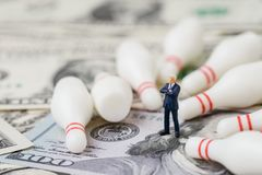 Devastating of stress financial trade war policy concept, miniature businessman president with knocked down bowling pins lying di stock image