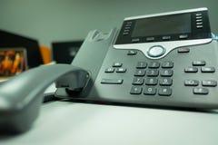 Deveice för telefon för Closeuptangentbordsip på kontorsskrivbordet royaltyfria foton