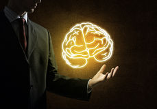 Develop our mind ability. Close up of businessman hand holding brain in palm Royalty Free Stock Image