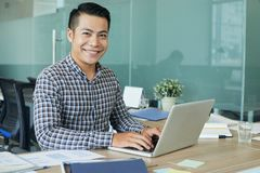 Developer busy with work. Smiling handsome developer working on laptop at his workplace in office royalty free stock photo