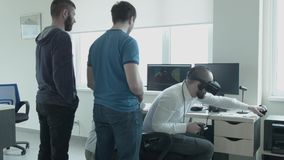 Developers of virtual reality games test the game they created. Tvoe young men look like the fourth man with glasses of