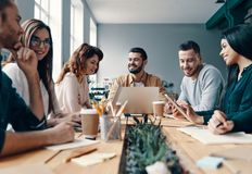 Developing business. Group of young modern people in smart casual wear discussing something and smiling while working in the creative office royalty free stock image