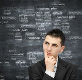 Developing a business plan. Young man thinking at a business plan Royalty Free Stock Photography