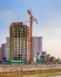 Developing high-rise residential building. Developing high-rise concrete residential building with crane stock photos