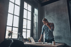 Developing new project using technologies. Serious young man talking on the mobile phone and working using laptop while standing near the office desk Royalty Free Stock Image