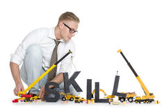 Developing skills: Businessman building skill-word. Building up skills concept: Focused businessman building the word skill along with construction machines Royalty Free Stock Photos