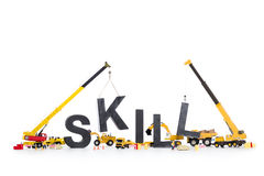 Developing skills: Machines building skill-word. Building up skills concept: Black alphabetic letters forming the word skill being set up by group of Royalty Free Stock Photography