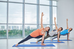 Developing strength. Group of women doing asana to develop strength royalty free stock images