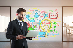 Development concept. Handsome young businessman using laptop in modern office interior with colorful business sketch on billboard. Development concept. 3D Stock Photo