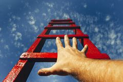 Development Motivation Career Growth Concept. Mans Hand Reaching For Red Ladder Leading To A Blue Sky. A male hand holds onto the crossbar of a red wooden Stock Photos