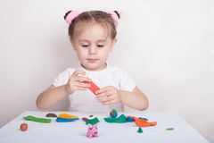 Girl sculpts from plasticine pink pig stock photo
