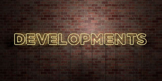 DEVELOPMENTS - fluorescent Neon tube Sign on brickwork - Front view - 3D rendered royalty free stock picture Royalty Free Stock Photography