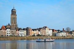 DEVENTER NEDERLÄNDERNA - DECEMBER 24, 2016: Färjan korsar floden IJssel med en sikt av den medeltida staden Arkivbild
