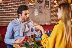 Devez l'alimenter Homme dans la chemise bleue mangeant et parlant avec l'amie images stock