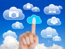 Device clouding. Businessman touching a virtual screen with digital clouds Royalty Free Stock Image