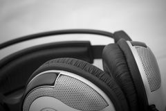 Device for listening of music. Blackly grey headphones on a grey background stock image