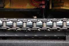 The device of a yellow loader on the railway. Gray steel chain links driving the forklift mechanism. The device of a yellow loader on the railway. Gray steel royalty free stock photography