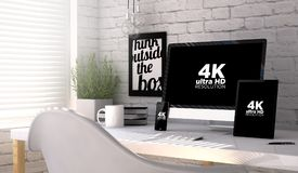 Devices with 4k resolution screen on a workplace mockup. Devices mock up with 4k ultra HD resolution screen on an hardwood desk. Screen graphics are made up Stock Photo