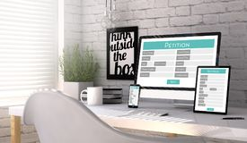 Devices with a petition form on the screen on a workplace mockup. Devices mock up with a petition online form on the screen on an hardwood desk. Screen graphics Stock Photos
