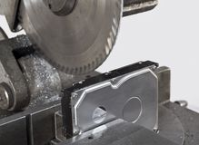 Deviding ha hard drive with a circular saw. Neutral backgound Stock Photography
