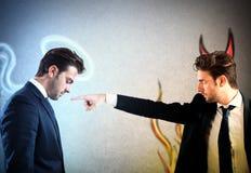 Devil accuses angel Stock Image