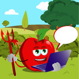 Devil apple holding laptop on a meadow Stock Photo