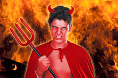 Devil boy. Male actor playing role of daemon on fire background Royalty Free Stock Photography