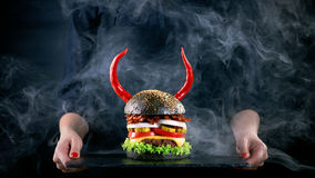 Devil burger with bacon and vegetables on black slat plate Royalty Free Stock Photo