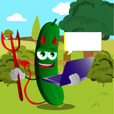 Devil cucumber or pickle holding laptop on a meadow Royalty Free Stock Photos