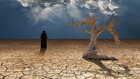 Devil in the desert. Dark cloaked figure in desert landscape Stock Images