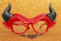 Devil disguise masquerade glasses. Isolated on a golden background royalty free stock photography