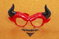 Devil disguise masquerade glasses. Isolated on a golden background stock photography