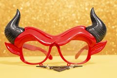 Devil disguise masquerade glasses. Isolated on a golden background royalty free stock photo