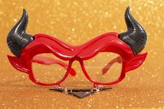 Devil disguise masquerade glasses. Isolated on a golden background stock image