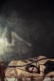 Devil from dreams. Innocent gothic girl sleeps in bed. Horned horrible devil stands behind the bed in smoke Royalty Free Stock Images