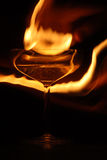 Devil drink. Luxurious wine glasses on a glass table with flames Royalty Free Stock Image