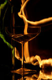 Devil drink. Luxurious wine glass with bottle on a glass table with flames Royalty Free Stock Photography