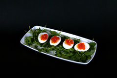 Devil eggs on white rectangular plate with red caviar and arugul Royalty Free Stock Photo