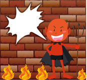 Devil and fire in front of brick wall Royalty Free Stock Photography