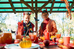 Devil girls. Two friendly girls standing by festive table prepared for Halloween stock photos